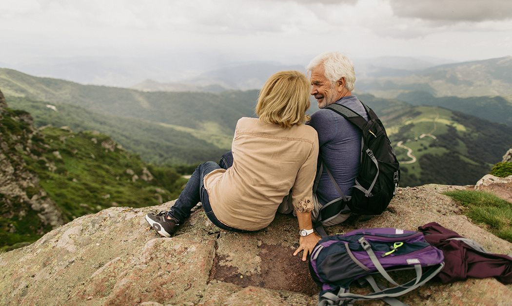 Retired couple sitting on hill side overlooking the view after backpacking