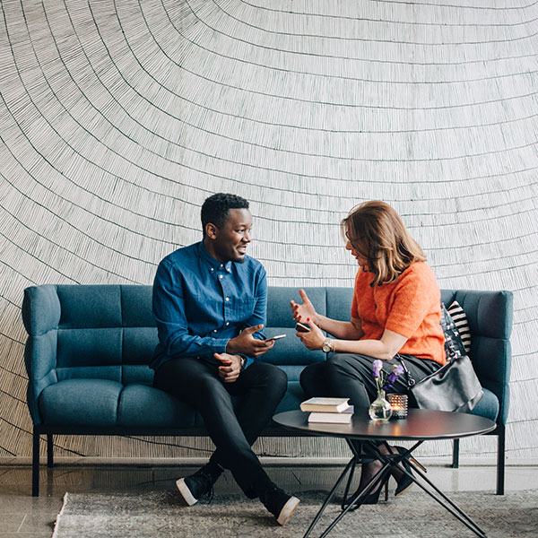 two people sitting on couch against white wall